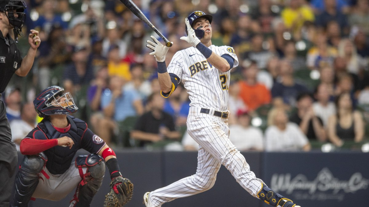 Milwaukee Brewers' Christian Yelich, right, reacts after mis-hitting a ball for an out during...