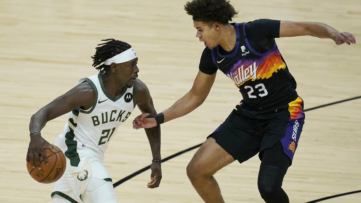 Milwaukee Bucks guard Jrue Holiday (21) drives against Phoenix Suns forward Cameron Johnson...