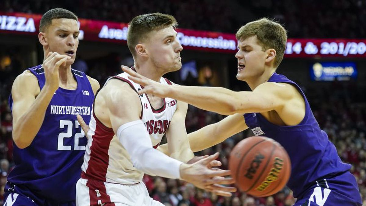 Wisconsin's Micah Potter (11) passes against Northwestern's Pete Nance (22) and Miller Kopp, right, during the second half of an NCAA college basketball game Wednesday, March 4, 2020, in Madison, Wis. Wisconsin won 63-48. (AP Photo/Andy Manis)