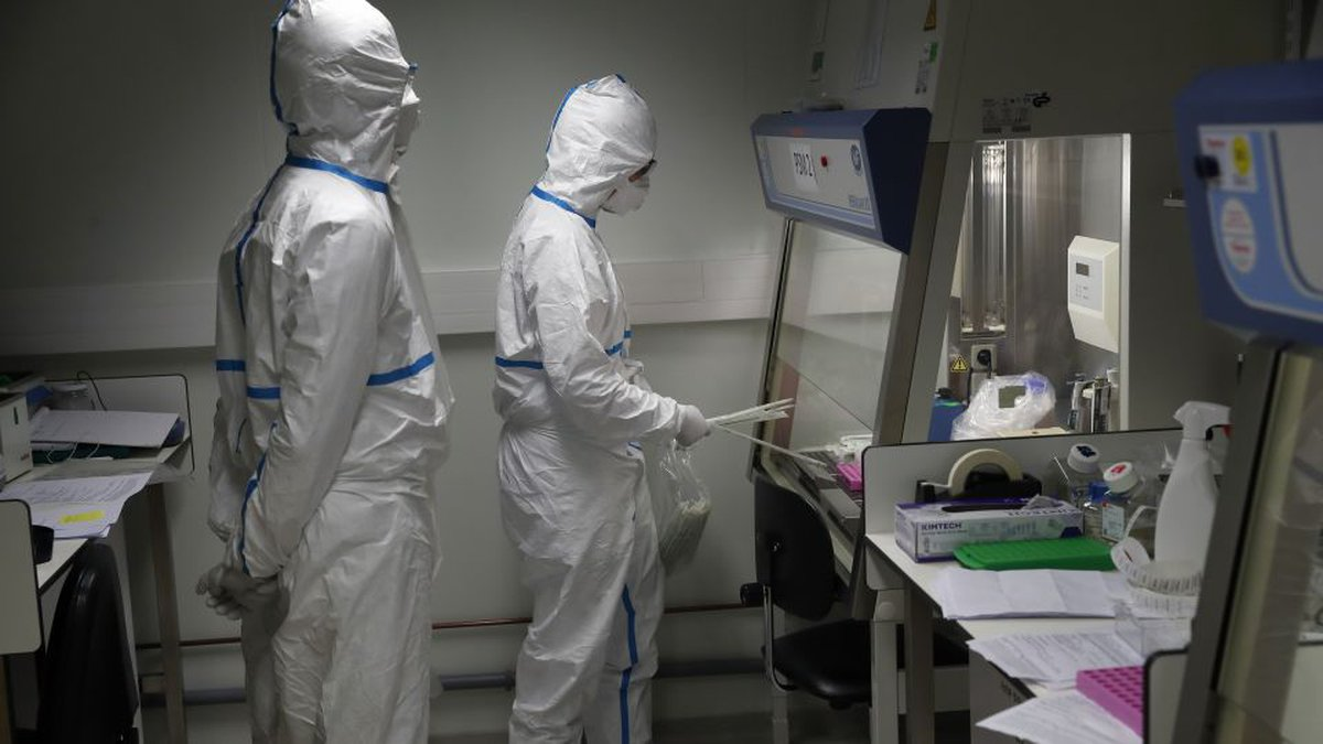 French lab scientists in hazmat gear inserting liquid in test tube manipulate potentially...