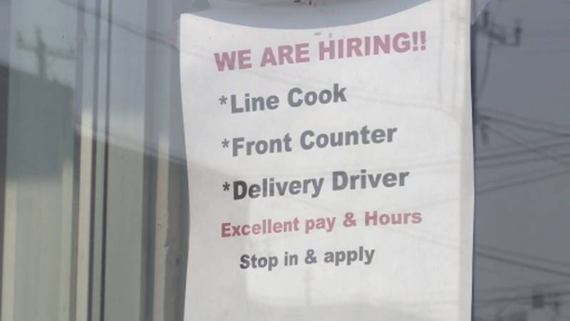A hiring sign hangs in the window of a business in Fort Atkinson. Many are looking to fill...