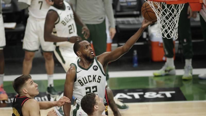 Milwaukee Bucks' Khris Middleton, center, shoots between multiple Atlanta Hawks defenders...