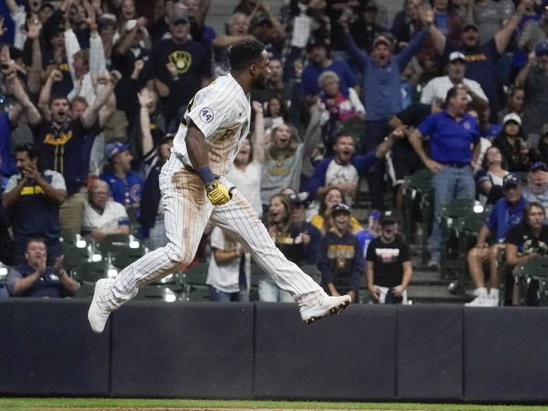 Milwaukee Brewers' Pablo Reyes scores reacts after scoring during the eighth inning of a...