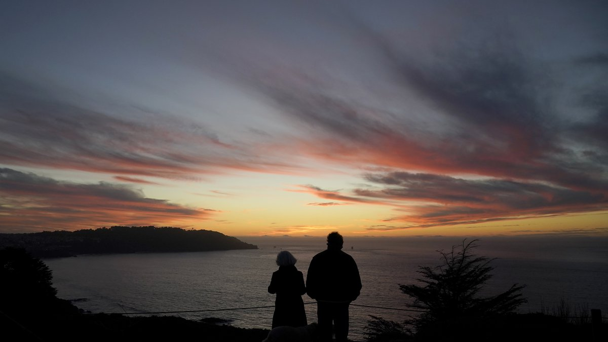 FILE - In this Dec. 21, 2020, file photo people watch as the sun sets from the Presidio in San...