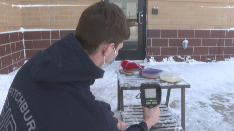 Fitchburg firefighter Cal McCreary uses thermal imaging camera to monitor the falling...