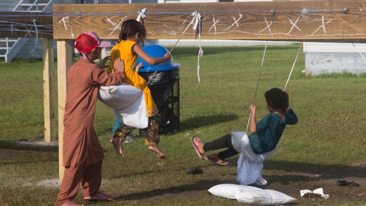 Children play on makeshift swings at Fort McCoy.