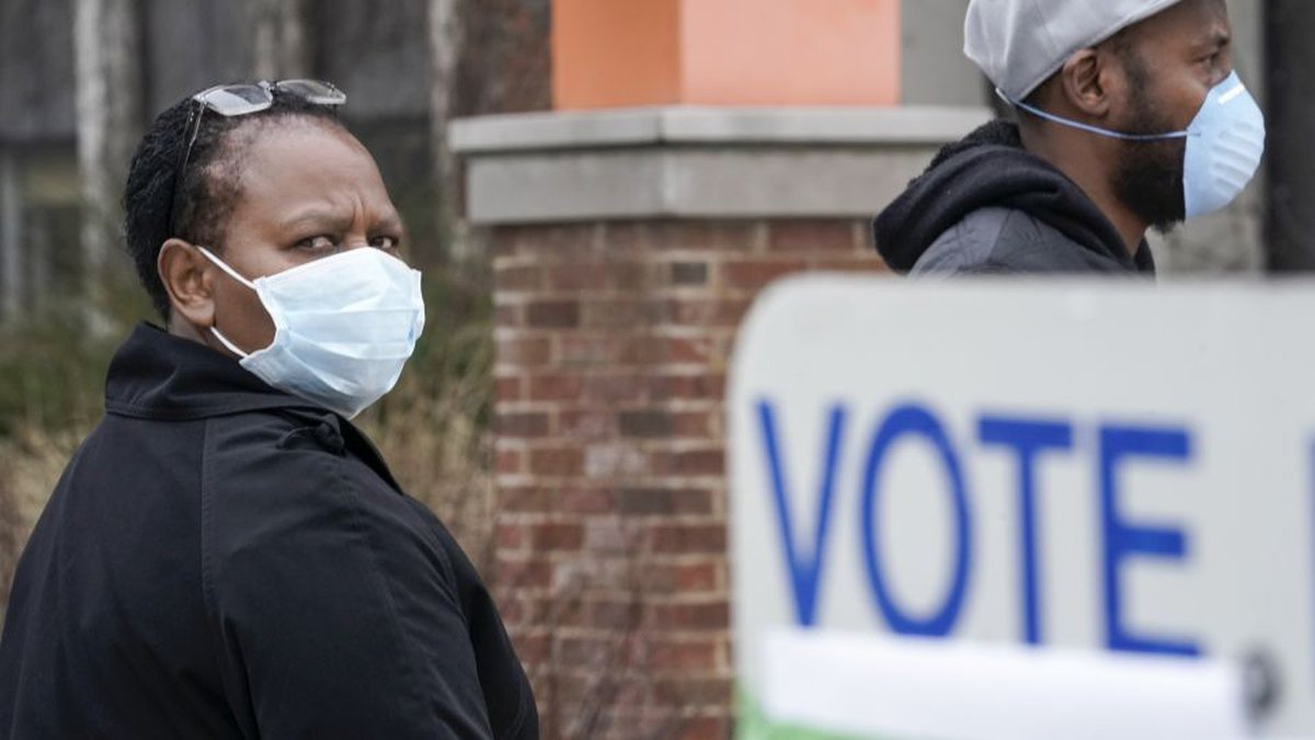 Voters masked against coronavirus line up at Riverside High School for Wisconsin's primary...