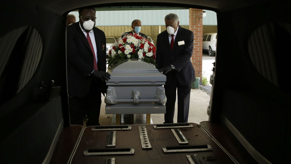 In this Saturday, April 18, 2020 photo, mortician Cordarial O. Holloway, foreground left,...