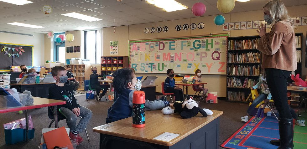 Kindergarten teacher Mrs. Amy Blake leads her full class in an in-person reading lesson.