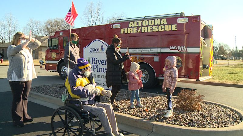 Retired Firefighter Bob Anderson, 98, waves to an Altoona Fire Truck with his family during a...