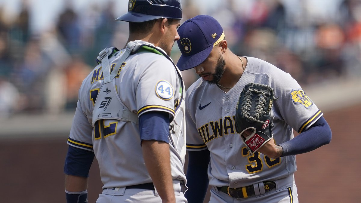 Milwaukee Brewers pitcher Devin Williams, right, meets on the mound with catcher Luke Maile...