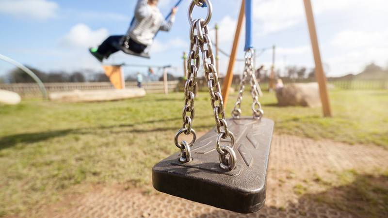 Empty playground swing with children playing in the background concept for child protection,...