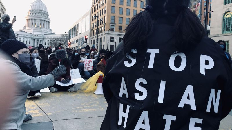 """A protester wears a """"Stop Asian Hate"""" hoodie in Downtown Madison Thursday night."""