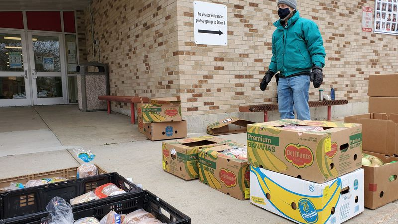 """Joe Wish with """"Food for Thought"""" waits for families outside Hawthorne Elementary School in..."""