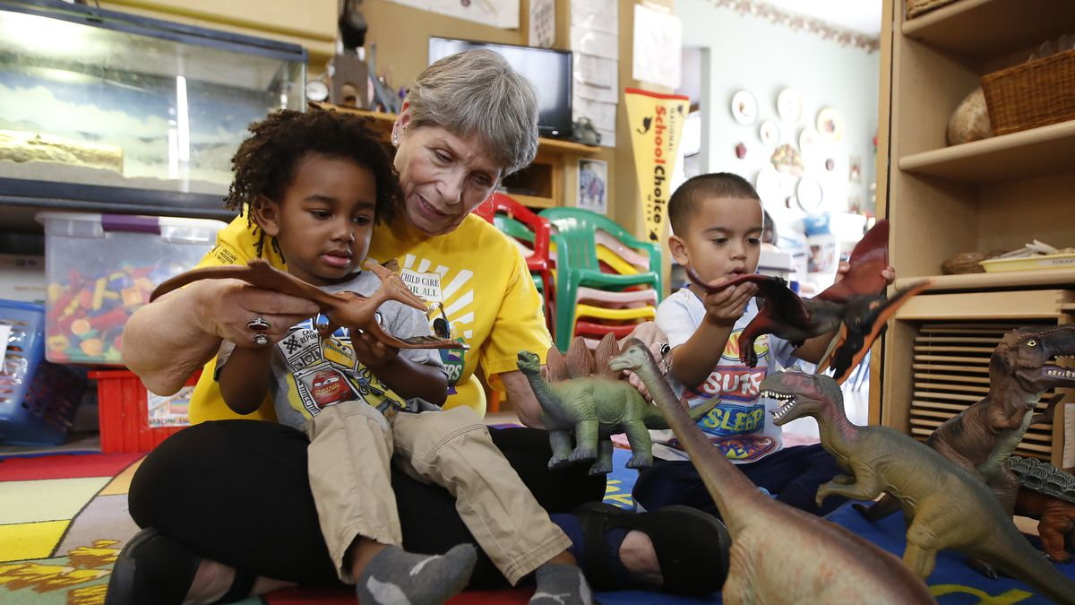 Child care provider Pat Alexander helps children, Isaiah, left, and Hector, right, identify...