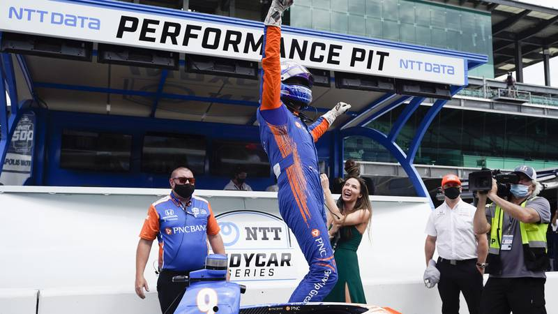 Scott Dixon, of New Zealand, celebrates with is wife, Emma Davies-Dixon, after winning the pole...