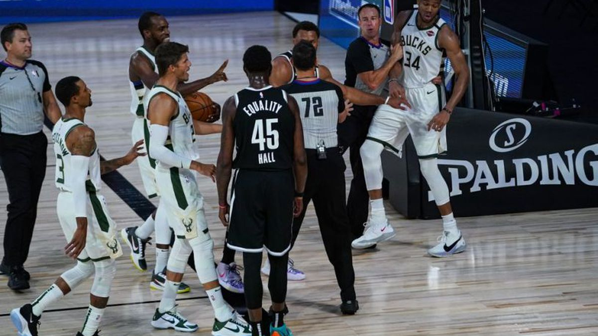 Referees separate players from the Milwaukee Bucks and Brooklyn Nets after a scuffle during the first half of an NBA basketball game Tuesday, Aug. 4, 2020 in Lake Buena Vista, Fla.