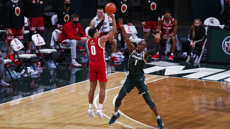 Wisconsin's D'Mitrik Trice, left, shoots against Michigan State's Joshua Langford during the...
