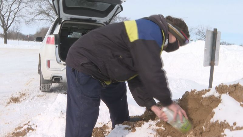 Madison resident Todd Femrite scopes up a bucket of sand to treat the sidewalks and driveways...