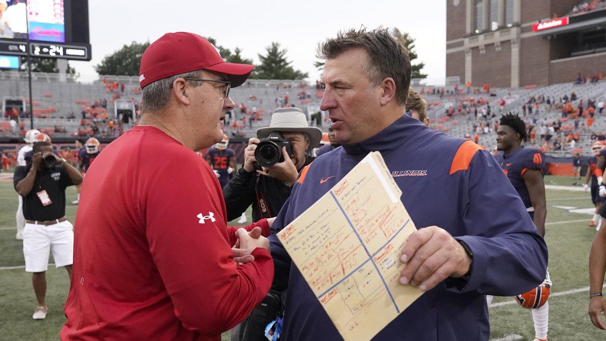 Wisconsin head coach Paul Chryst, left, and Illinois head coach Bret Bielema meet after an NCAA...