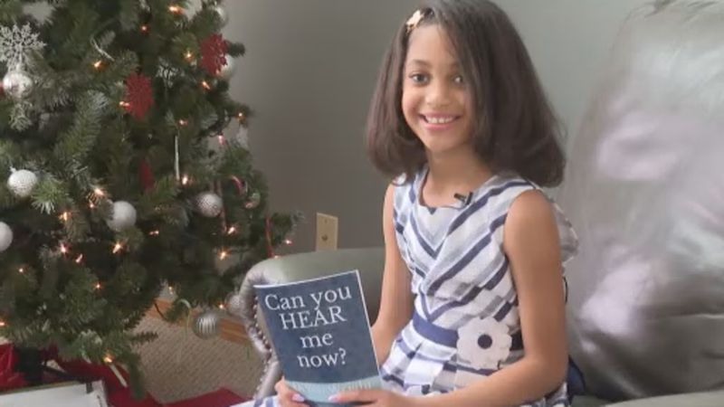 Demii Wright, 9, poses with her book, Can you HEAR me now?