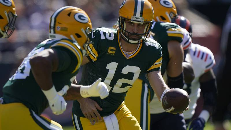 Green Bay Packers quarterback Aaron Rodgers (12) hands the ball off to running back A.J. Dillon...