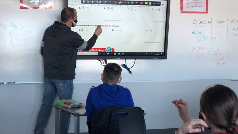 A Waunakee teacher solves a math problem for his students.