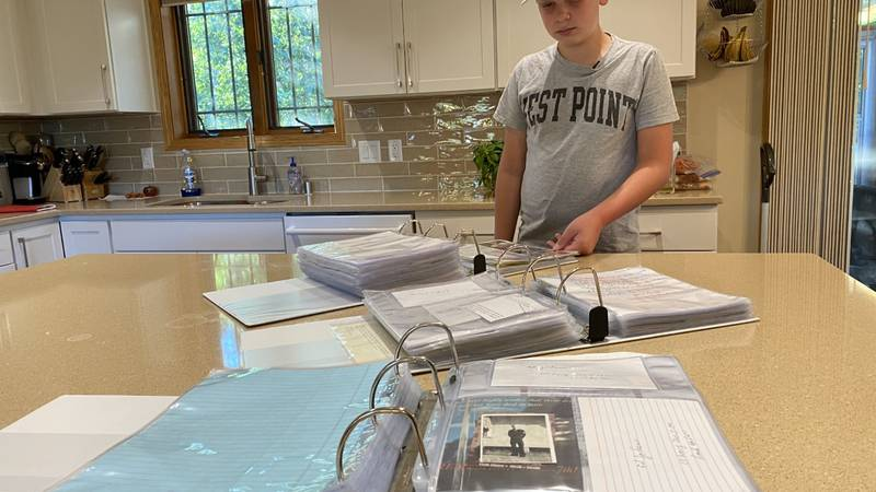 Henry Schoepke, 13, shows his collection of WWII veteran signatures, letters and memorabilia.