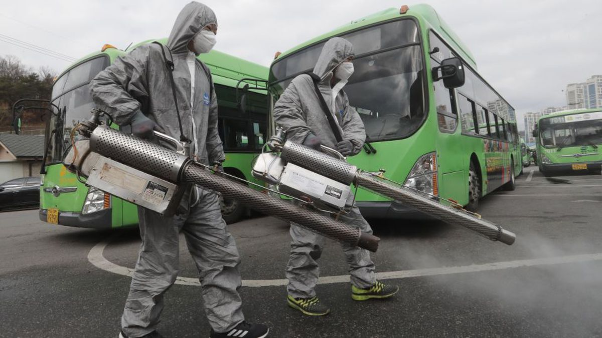 Workers wearing protective suits spray disinfectant as a precaution against the coronavirus at a bus garage in Seoul, South Korea, Wednesday, Feb. 26, 2020. The number of new virus infections in South Korea jumped again Wednesday and the U.S. military reported its first case among its soldiers based in the Asian country, with his case and many others connected to a southeastern city with an illness cluster. (AP Photo/Ahn Young-joon)