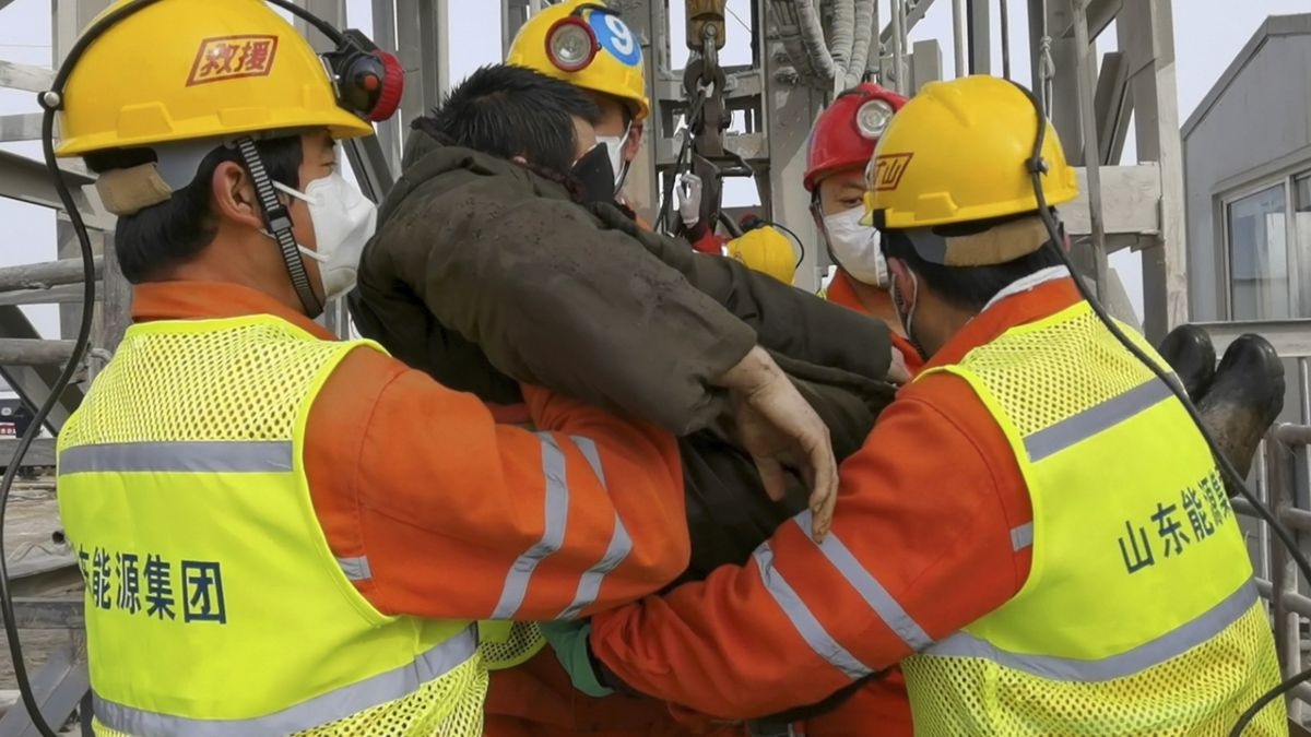In this photo released by Xinhua News Agency, rescuers carry a miner who was trapped in a gold...