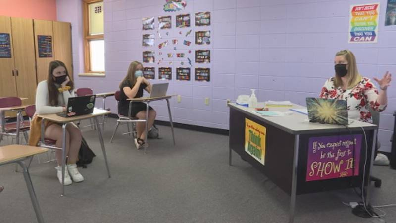 English teacher Nicole Giessel and two of her students, Brynna Malone and Grace Rabl, discuss...