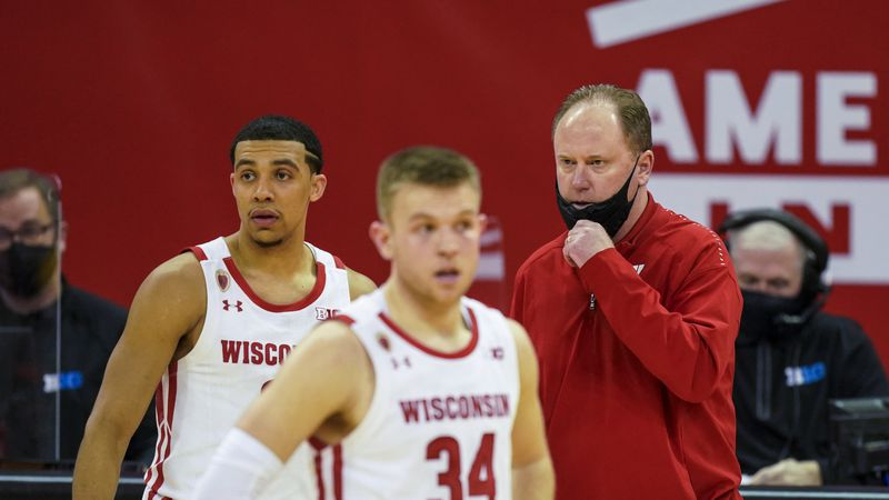 Wisconsin coach Greg Gard talks with D'Mitrik Trice, left, and Brad Davison during the second...
