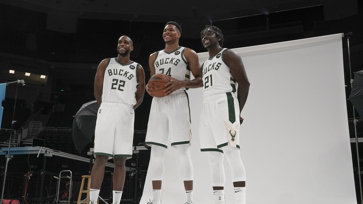 Milwaukee Bucks' Giannis Antetokounmpo is flanked by Khris Middleton and Jrue Holiday as they...