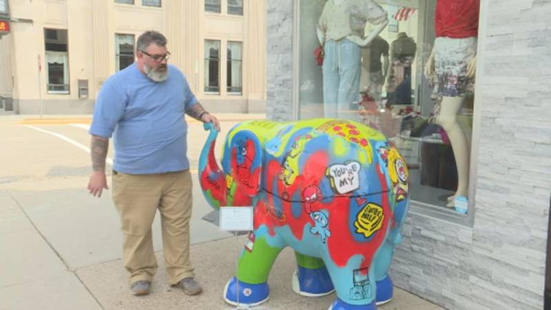 """A Baraboo artist shows off his piece """"Bizzy"""" as part of the Parade of Elephants exhibit."""