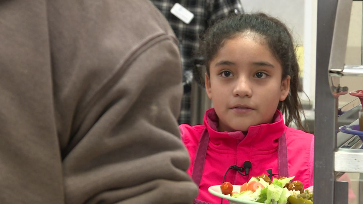 A 9-year-old volunteer serves food at the St. Martin House.