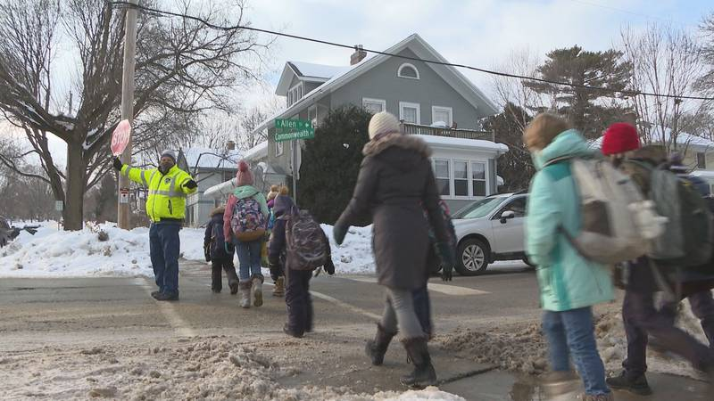 Terry Tappy guides a group of students across the street