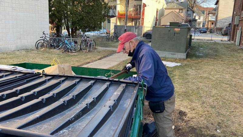 Gary Gates retrieves beverage cans from a garbage dumpster.
