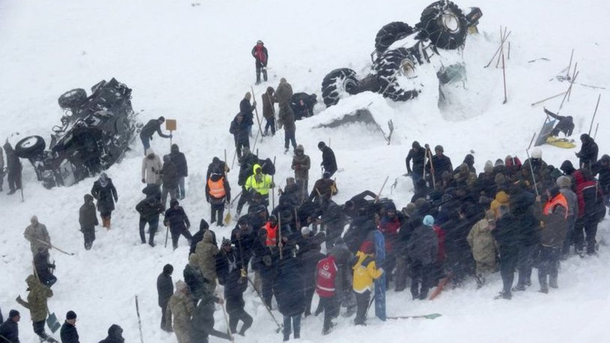 Emergency service members work in the snow around overturned vehicles, near the town of...
