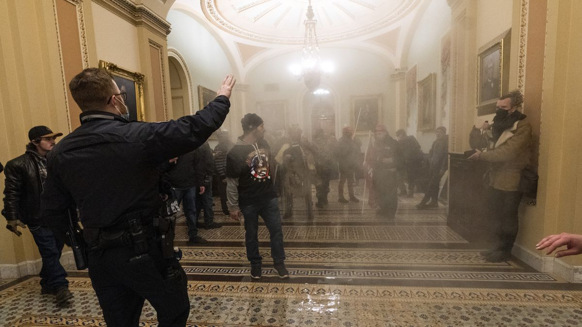 In this Wednesday, Jan. 6, 2021 file photo smoke fills the walkway outside the Senate Chamber...