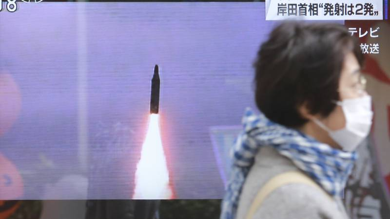 ADDS FILE FOOTAGE - A woman walks past a TV screen showing a file footage of a North Korean...