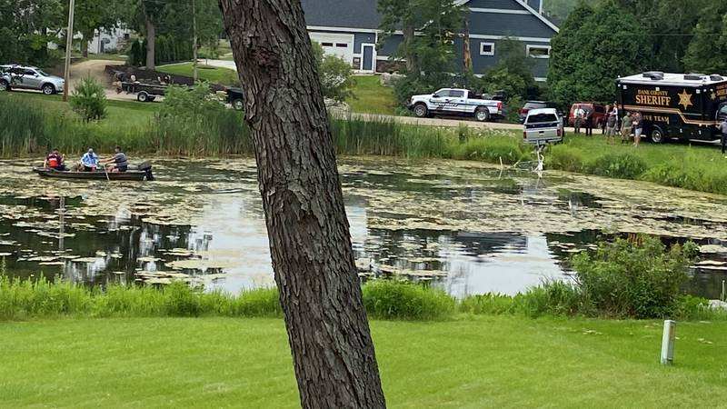 Authorities search a pond near the home of Bart and Krista Halderson, on July 21, 2021.