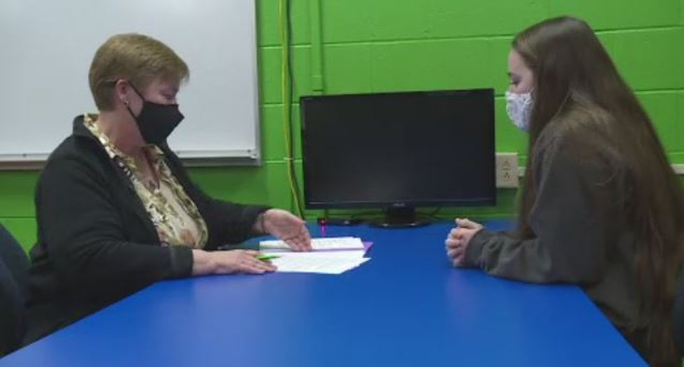 Wells works with a high school junior to determine which classes she is interested in taking...