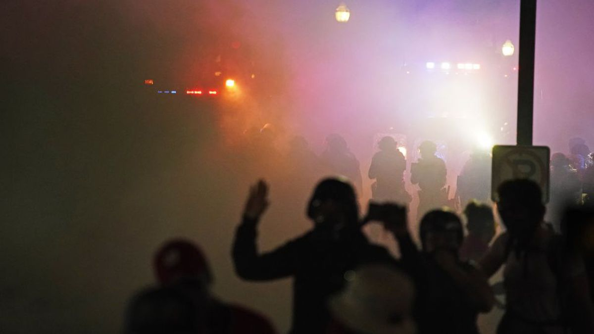 Police in riot gear clear the area in front of Kenosha County Courthouse during clashes with...