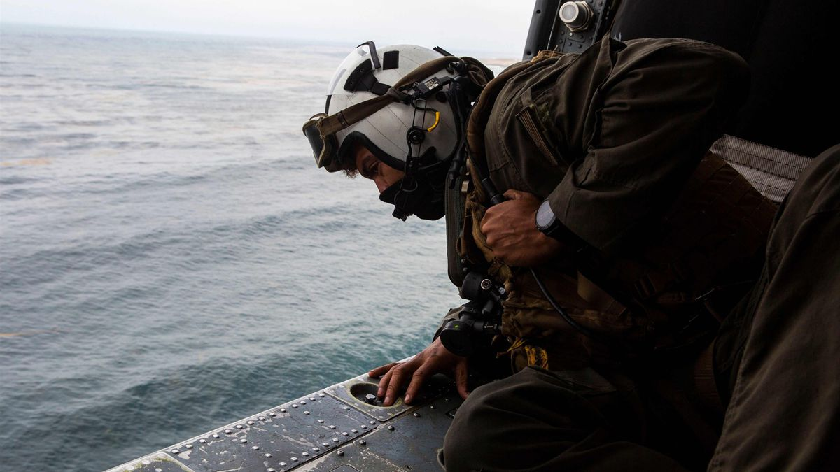 This US Marine Corps handout photo shows Naval Air Crewman 2nd Class Joseph Rivera, a search and rescue swimmer assigned to the amphibious assault ship USS Makin Island (LHD-8), looking out of a US Navy MH-60 Seahawk while conducting search and rescue relief operations following an AAV-P7/A1 assault amphibious vehicle mishap off the coast of Southern California on July 30, 2020.Mackenzie Binion/US Marine Corps / AFP - Getty Images