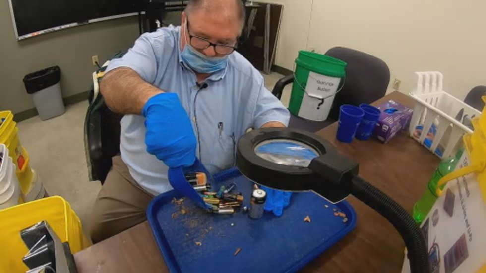 One man works to sort recycled batteries by hand.
