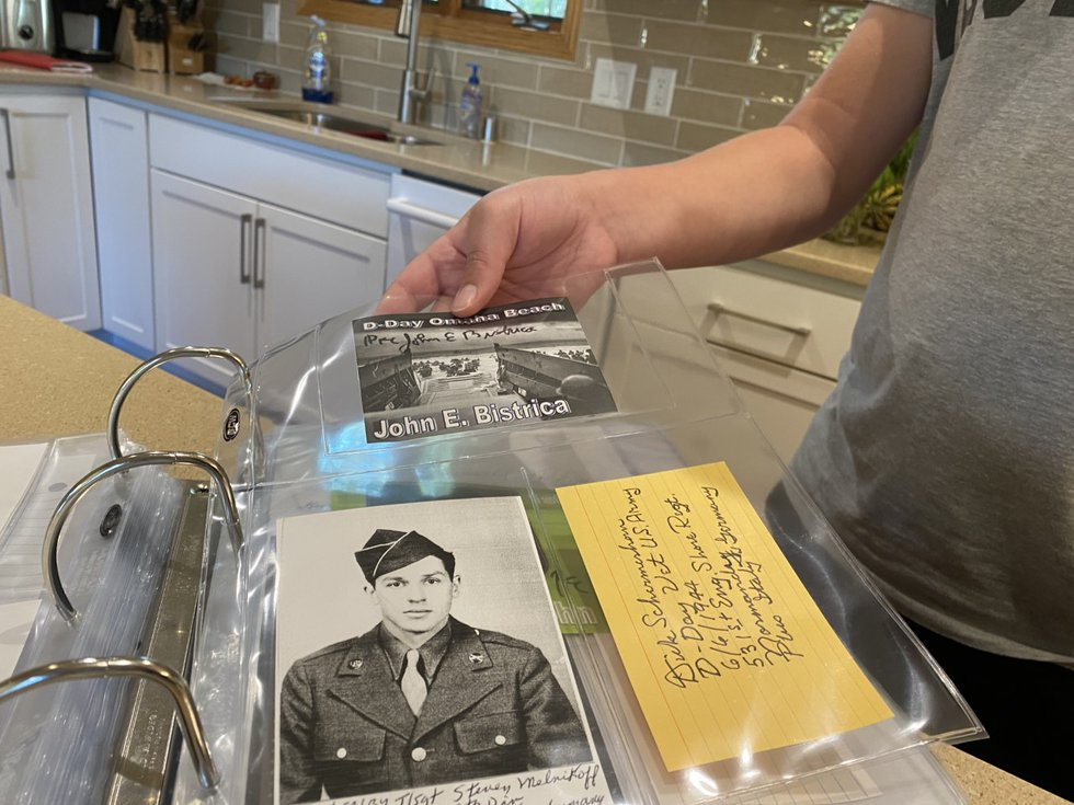 Henry Schoepke shows pictures and notes sent to him by WWII veterans