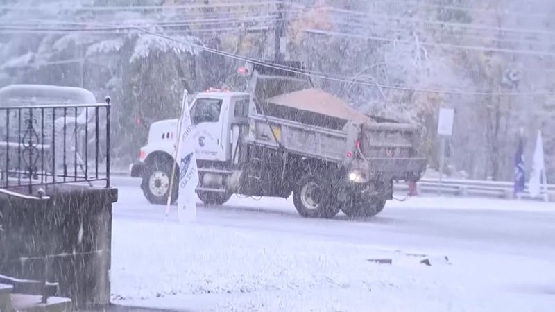 Salt truck pours salt on the road during large snowstorm