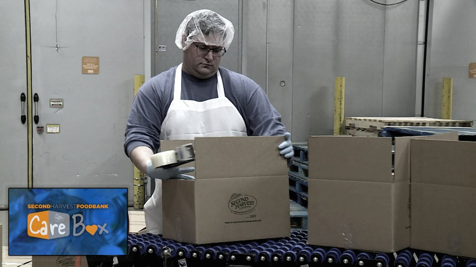 Volunteer putting together Care Boxes at Second Harvest Foodbank of Southern Wisconsin. (WMTV)