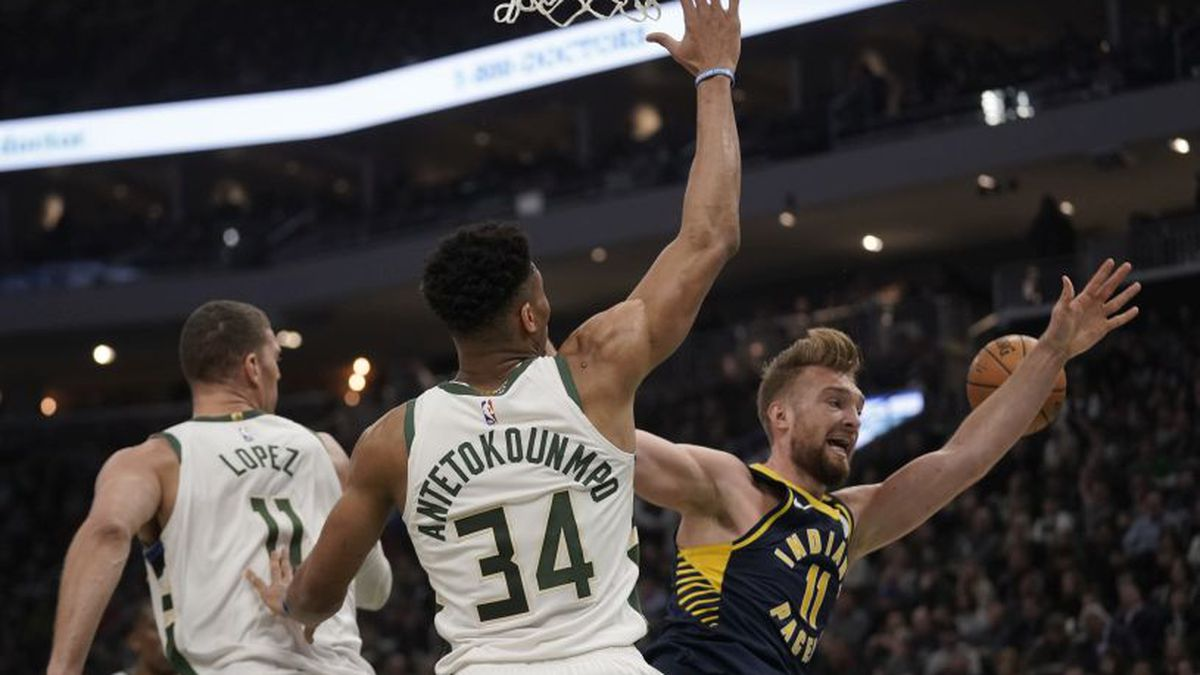 Indiana Pacers' Domantas Sabonis is fouled as he drives past Milwaukee Bucks' Brook Lopez and...
