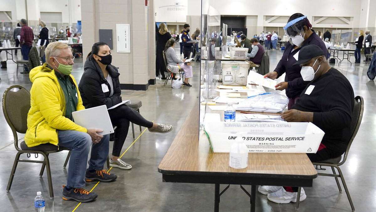 FILE - In this Nov. 20, 2020 file photo, election workers, right, verify ballots as recount...